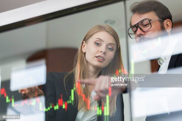 businesswoman and businessman talking profit on  futuristic display - hud graphical user interface stock photos and pictures