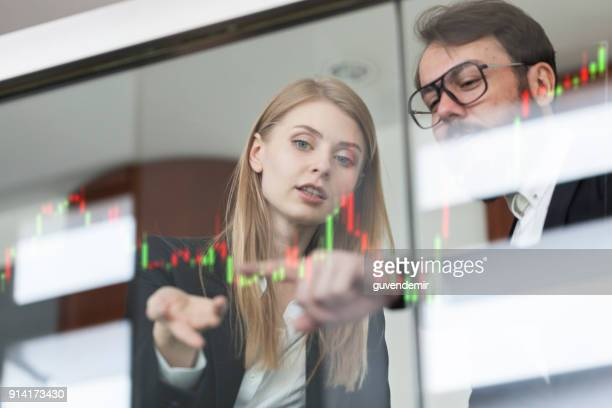 businesswoman and businessman talking profit on futuristic display - financial technology stock photos and pictures