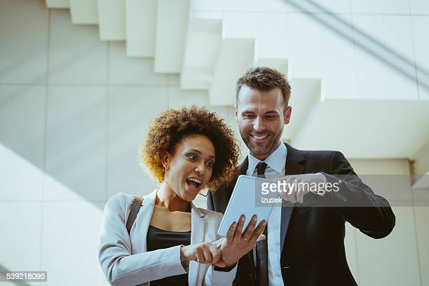 businesswoman and businessman using a digital tablet - izusek stock pictures, royalty-free photos & images