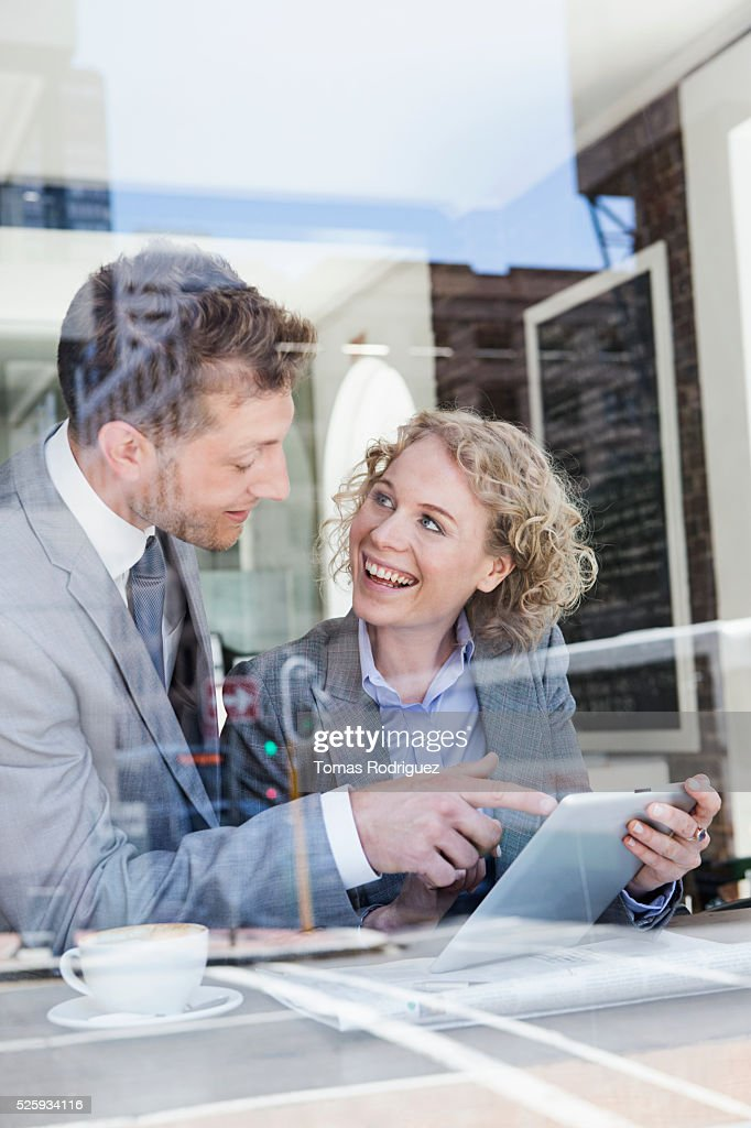 Businesswoman and businessman using tablet PC in cafe : Stock-Foto