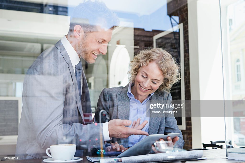 Businesswoman and businessman using tablet PC in cafe : Photo