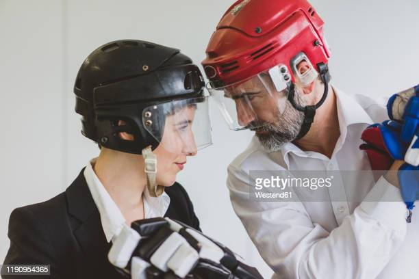 businesswoman and businessman wearing ice hockey equipment in office - ice hockey player stock pictures, royalty-free photos & images