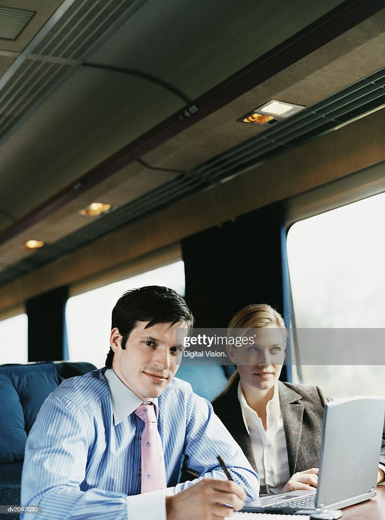 Businesswoman and Businessman Working in a Train : Stock Photo
