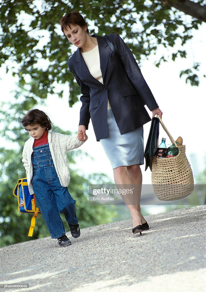 Businesswoman and child holding hands, walking : Stockfoto