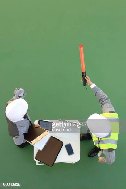 businesswoman and construction worker pointing