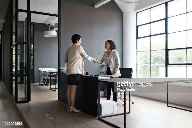 businesswoman and coworker shaking hands in office - cream coloured blazer stock pictures, royalty-free photos & images