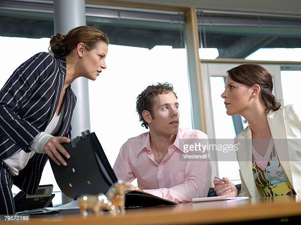 Businesswoman and co-workers in office, discussing