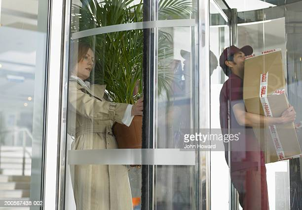 Businesswoman and deliveryman stuck in revolving door