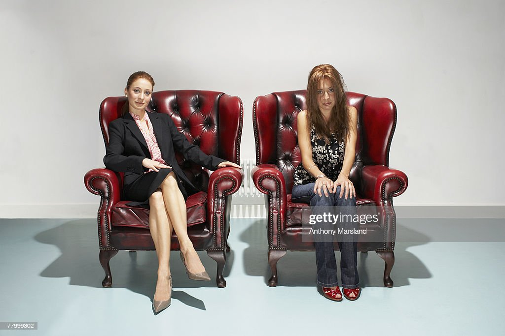 Businesswoman and disheveled woman in comfy leather chairs : Stock Photo