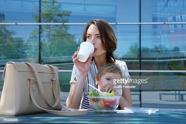 Businesswoman and her child eating lunch together outside.