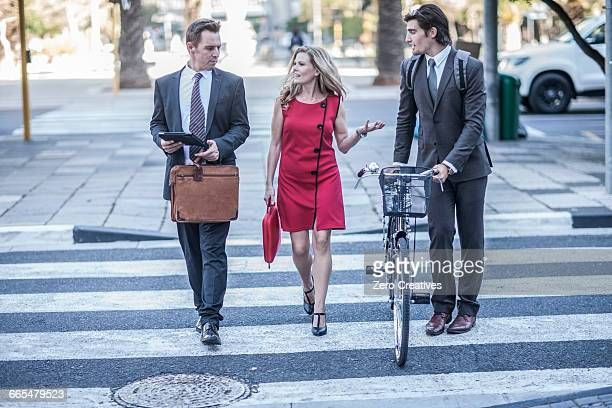Businesswoman and male colleagues talking whilst crossing road