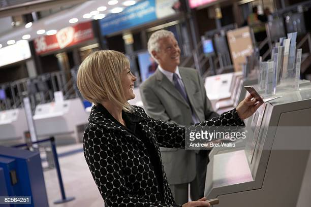 businesswoman and man at airport check-in desk