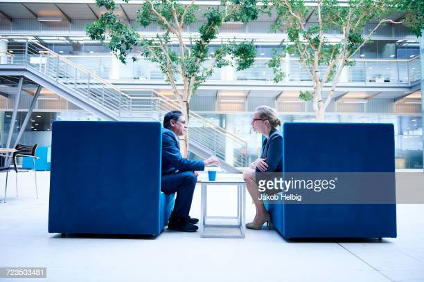 Businesswoman and man at meeting in office atrium armchairs