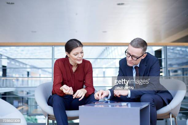 Businesswoman and man having meeting on office balcony
