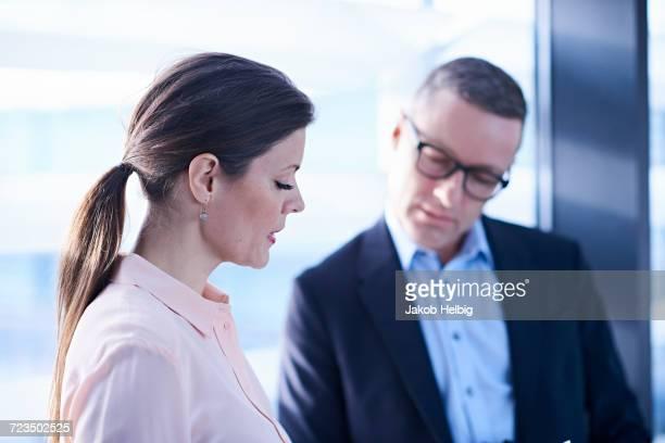businesswoman and man looking down in office - down blouse stockfoto's en -beelden