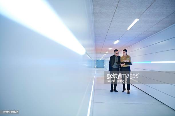 Businesswoman and man reading file in office corridor
