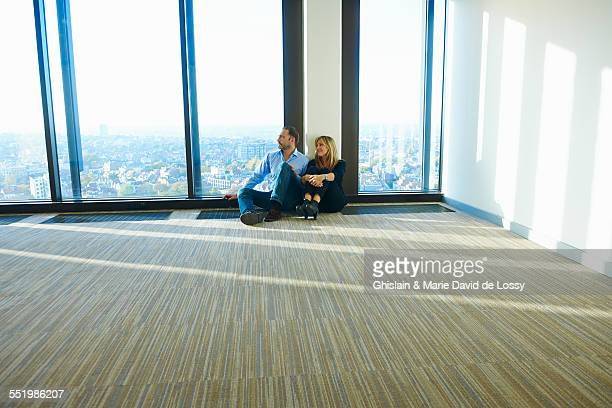 Businesswoman and man sitting in front of window in empty skyscraper office, Brussels, Belgium