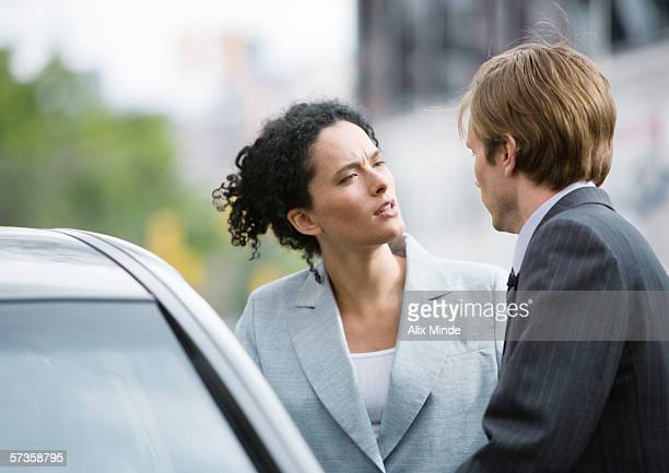 Businesswoman and man speaking next to car