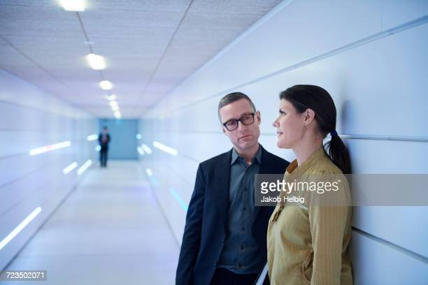 Businesswoman and man talking in office corridor