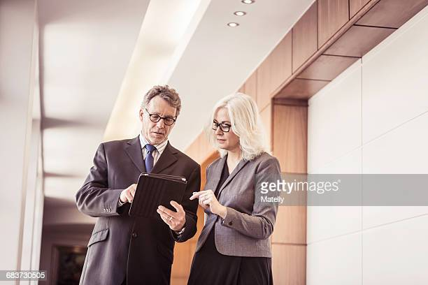 Businesswoman and man using digital tablet in office corridor