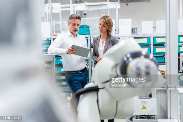 businesswoman and man with tablet talking at assembly robot in a factory - robot arm stock pictures, royalty-free photos & images
