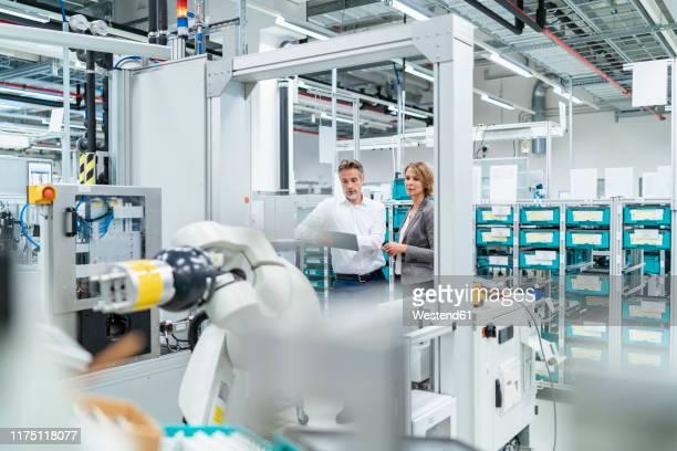 businesswoman and manwith tablet talking in a modern factory - rechnerunterstütztes konstruieren stock-fotos und bilder