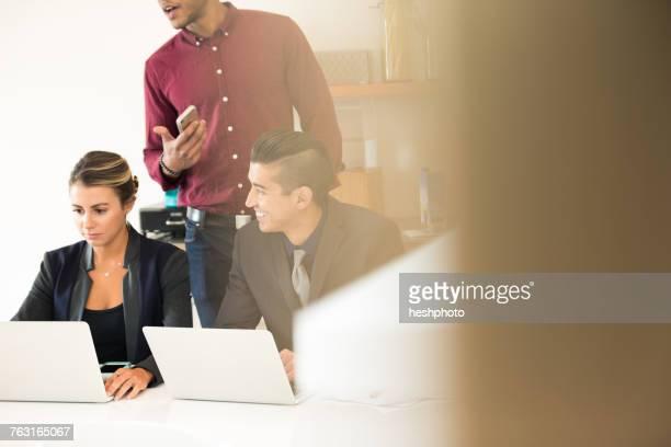 businesswoman and men having meeting at office desk - heshphoto stock-fotos und bilder