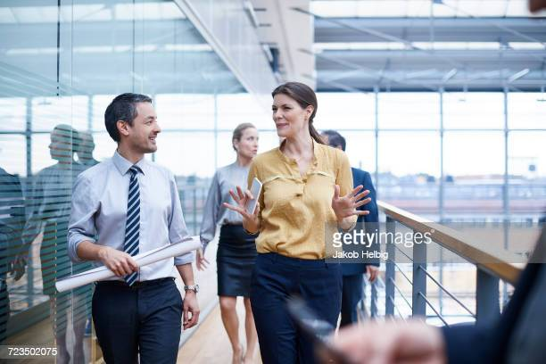 Businesswoman and men walking and talking on office balcony