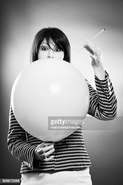 businesswoman and the risk of puncturing a baloon - puncturing stock pictures, royalty-free photos & images