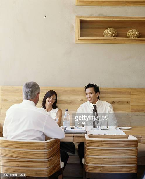 Businesswoman and two businessmen having lunch meeting, smiling