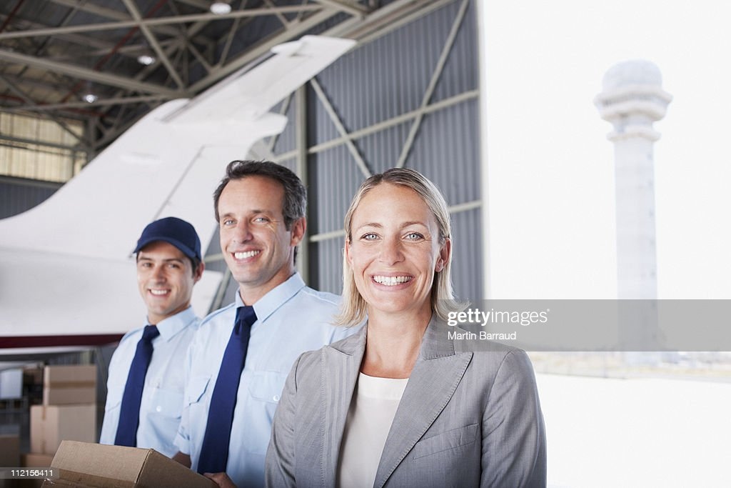 Businesswoman and workers standing in hangar : Stock Photo