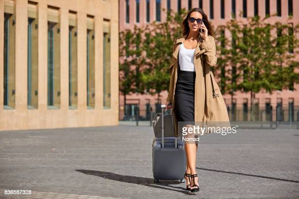 businesswoman answering call while pulling luggage - skirt stock pictures, royalty-free photos & images