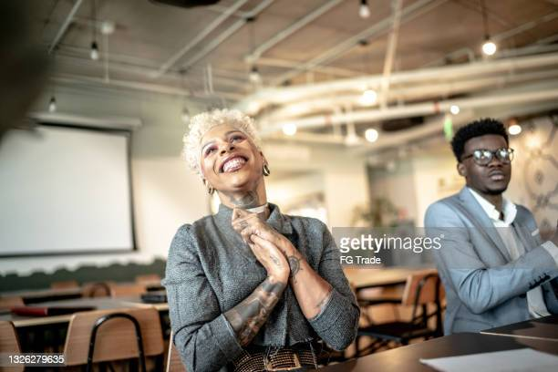businesswoman applauding at business meeting - applauding stock pictures, royalty-free photos & images