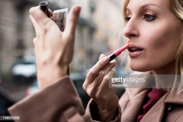 Businesswoman applying lipstick outdoors