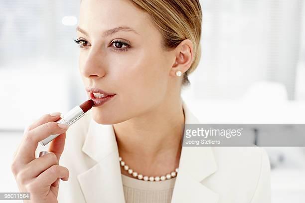 Businesswoman applying lipstick