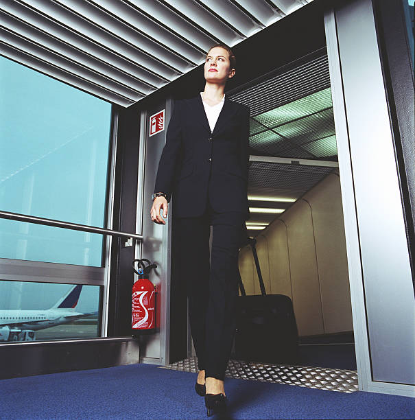 Businesswoman arriving at airport terminal, low angle view