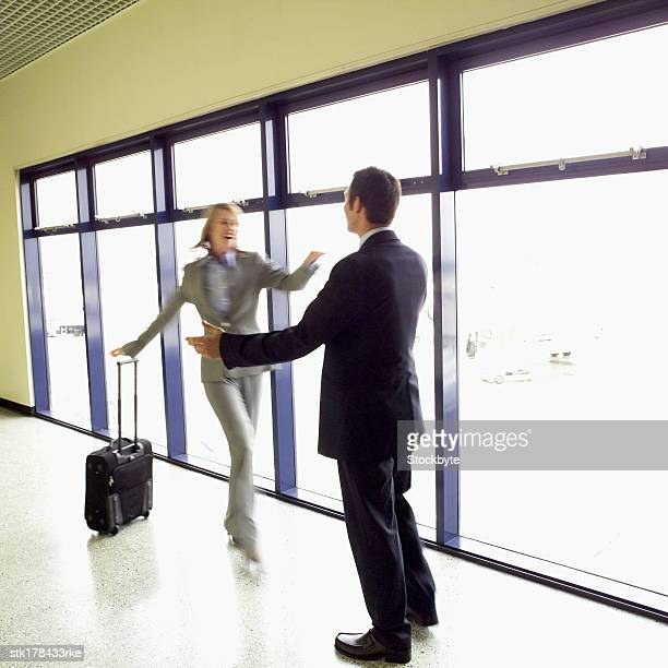 businesswoman arriving at airport with luggage and hugging businessman