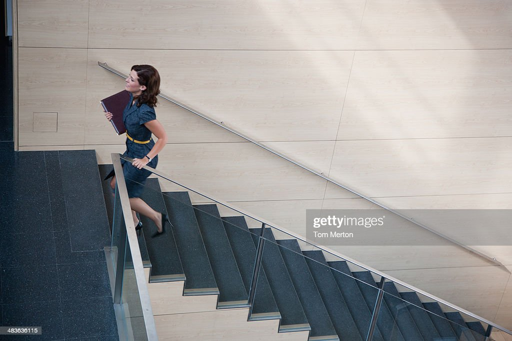 Businesswoman ascending office staircase : Stock Photo