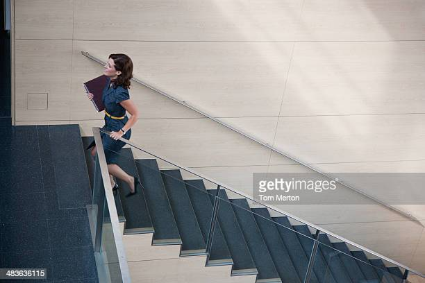 businesswoman ascending office staircase - striding stock pictures, royalty-free photos & images