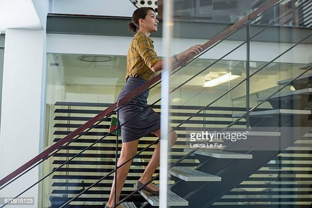 businesswoman ascending office staircase - degraus e escadas - fotografias e filmes do acervo