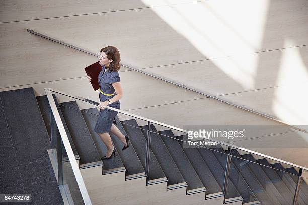 businesswoman ascending office staircase - stairs stock photos and pictures