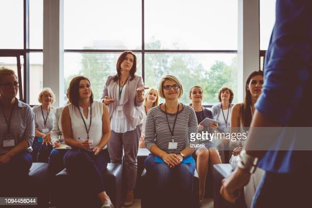 businesswoman asking question during seminar - press conference stock pictures, royalty-free photos & images