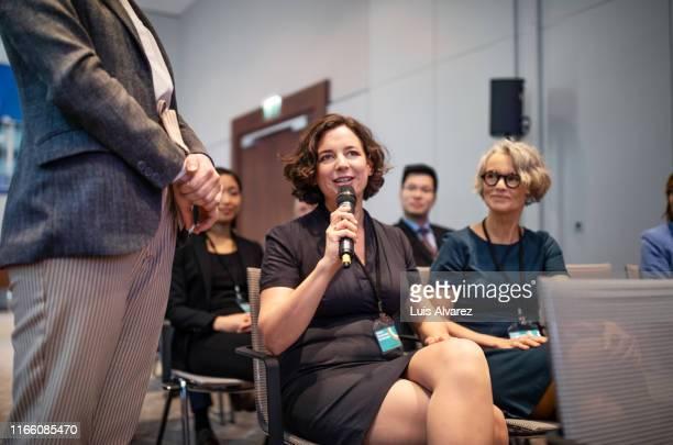 businesswoman asking questions during a seminar - parte do meio - fotografias e filmes do acervo