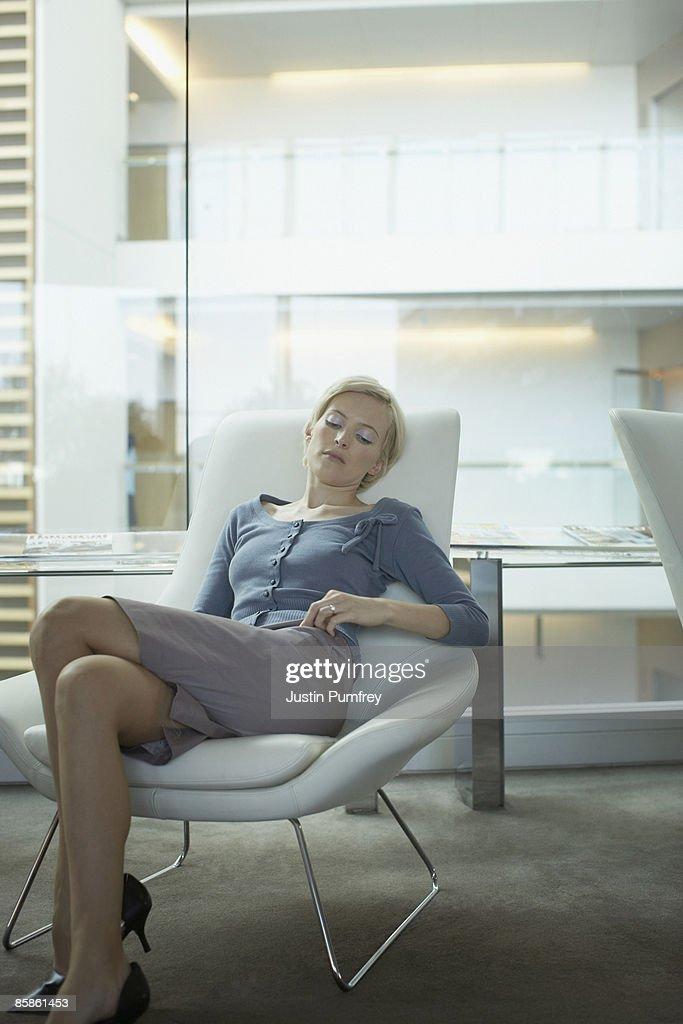 Businesswoman asleep in chair : Stock-Foto