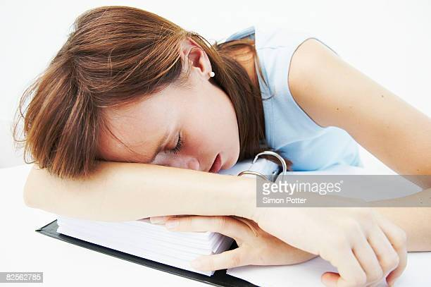 Businesswoman asleep over file