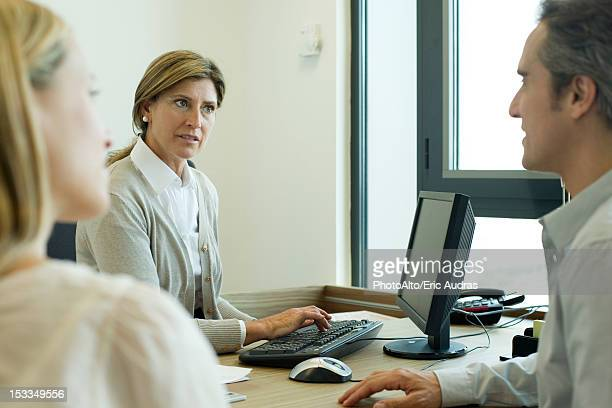 Businesswoman assisting clients in office
