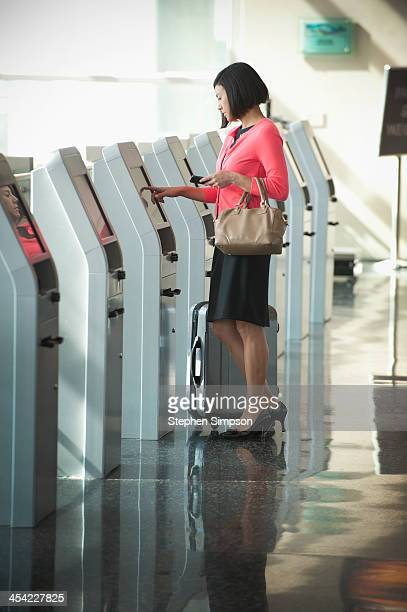 businesswoman at airport, electronic ticket dispen