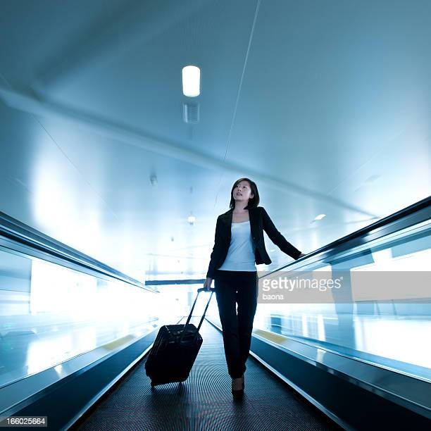 businesswoman at airport - pedestrian walkway stock pictures, royalty-free photos & images