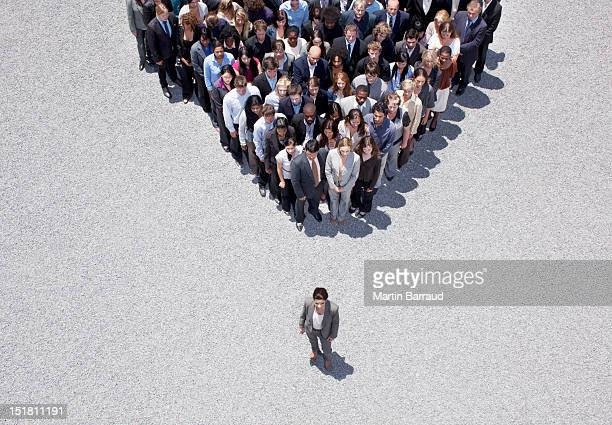 businesswoman at apex of crowd - individuality stock photos and pictures