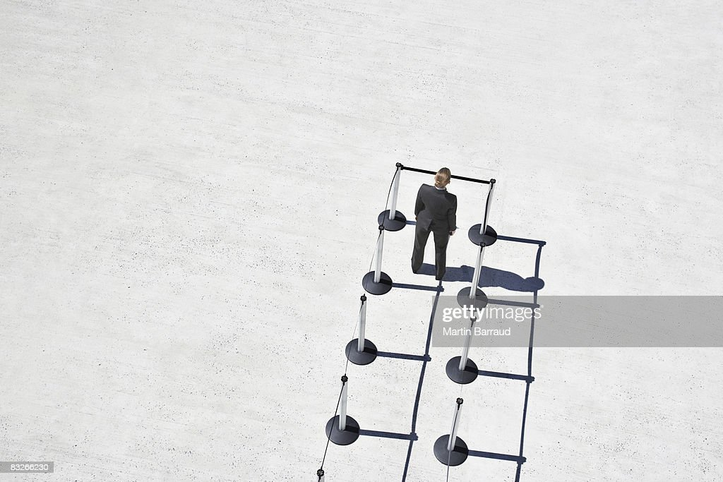 Businesswoman at blocked end of cordon posts : Stock Photo